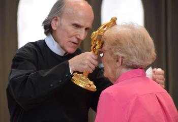 Father Michalik assists a member of the faith in venerating a relic of St. John Neumann.