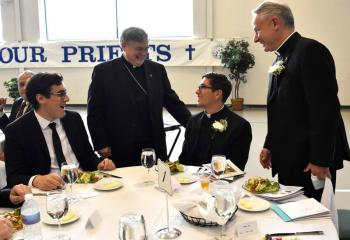 Bishop of Allentown Alfred Schlert, second from left, talks with, from left, a diocesan seminarian, Father Esposito and Father Maria during the dinner.