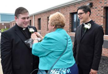 Paulette Roth presents a flower to Father Wehr, left, and Father Esposito.