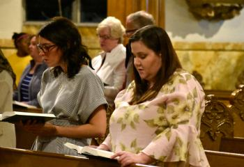 Faithful participate in Benediction during the service.