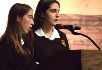 Bethlehem Catholic students Deirdre Kelly, left, and Samantha Hoffman sing the opening hymn at the morning liturgy.